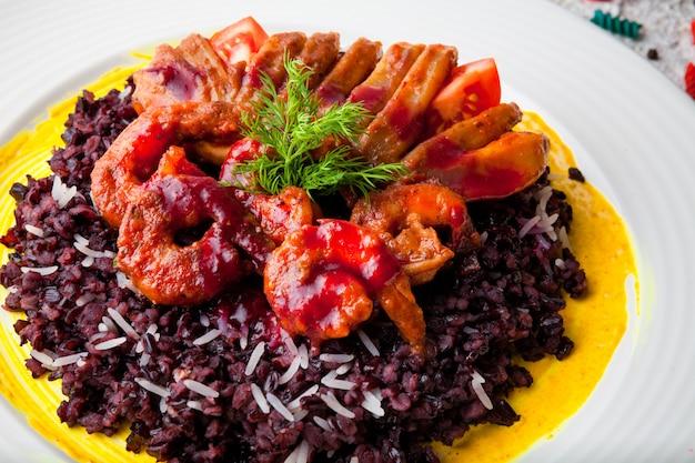 Сверху креветки в кляре с красным рисом и зеленью в белой тарелке