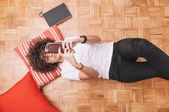 From above teenager using smartphone on floor
