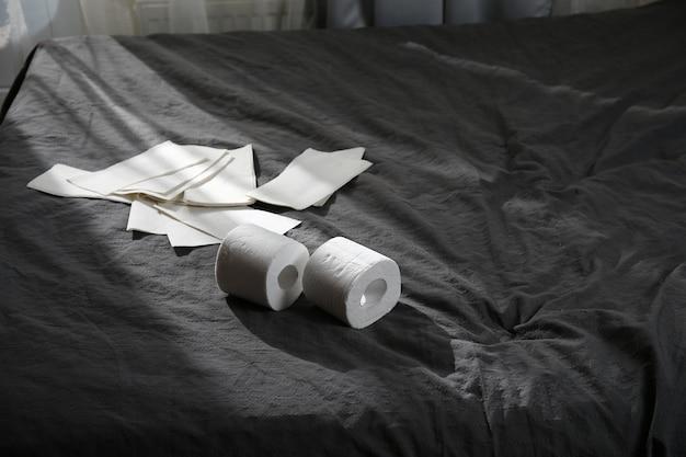 Сверху два рулона туалетной бумаги на кровати, лежа на кровати, покрытой серой простыней в спальне