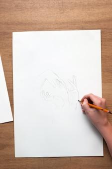 펜 실로 손으로 스케치를 그리는 인식 할 수없는 사람 위에서