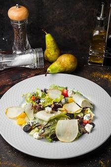 上から、白い皿に梨とコショウ、塩とオリーブオイルの野菜サラダ