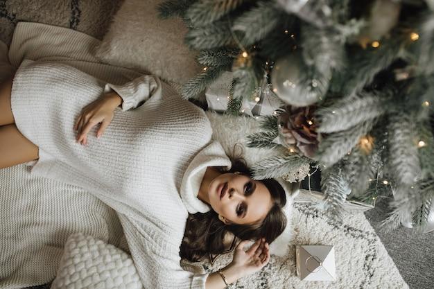 Сверху девушка лежит возле елки