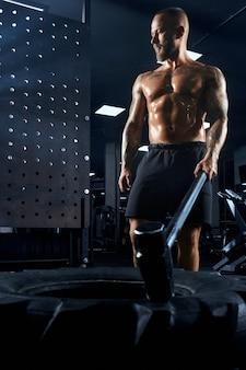 大きなハンマーを手に持っている筋肉質の白人男性の上のビューから。