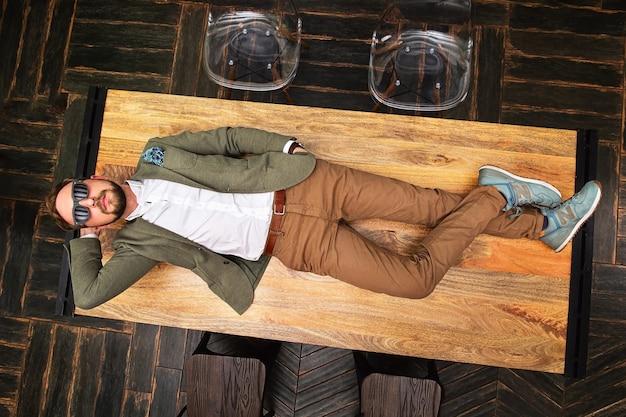 나무 탁자에 누워 있는 잘생긴 청년의 위에서