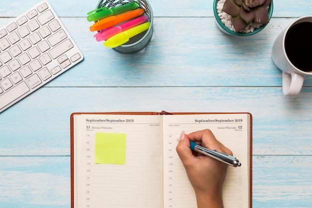 Сверху женщина пишет в дневнике