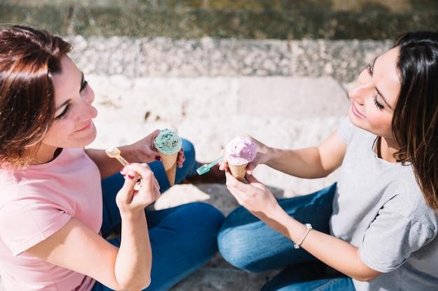 Сверху женщины едят мороженое