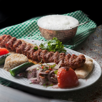 From above adana kebab with rice and fried vegetables and chopped onion and ayran