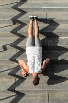 From above athletic man doing push ups on stairs