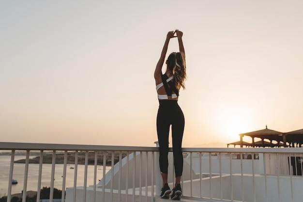 Сзади сексуальная молодая женщина в спортивной одежде на набережной на восходе солнца. летнее утро в тропической стране, тренировка, модная модель, фитнес, счастье.