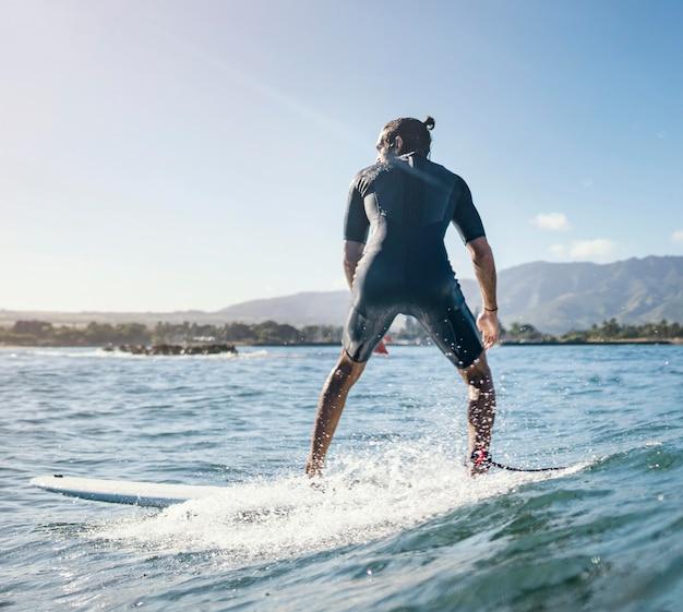 Dall'uomo surfista girato indietro all'aperto