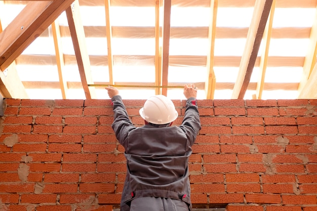 From below back view of man in hardhat measuring width of ceiling with wooden beams