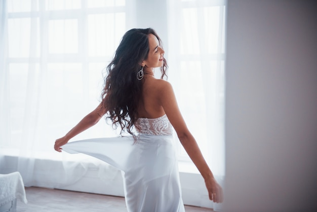 From behind. beautiful woman in white dress stands in white room with daylight through the windows