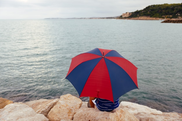 雨が降っている間、海のそばで傘を持って岩の上に座っている匿名の男性の後ろから