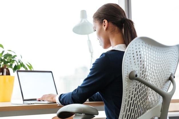 下の画像から、テーブルのそばに座って窓際でラップトップを使用しているアフロビジネスウーマンの画像。