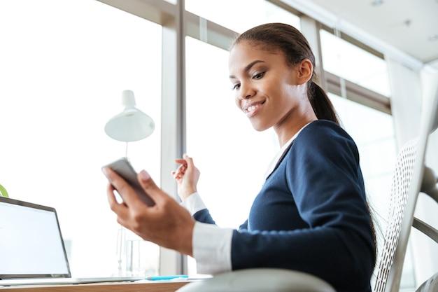 下からオフィスで電話を見ているドレスを着た笑顔のアフロビジネス女性の画像
