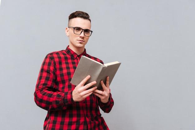 Снизу изображение молодого серьезного человека в очках и красной рубашке, читающей книгу в студии. изолированный серый фон