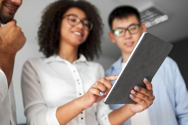 Снизу веселая женщина держит планшет и указывает на экран, стоя с коллегами-мужчинами в офисе и вместе обсуждая бизнес-проект