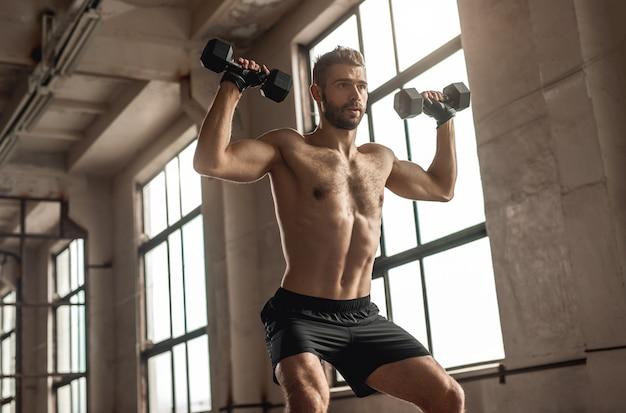 체육관에서 기능적 피트니스 운동을하는 동안 무거운 아령으로 쪼그리고 앉는 강한 남성 운동 선수 아래에서
