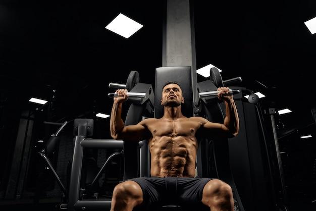Вид снизу бородатого мускулистого мужчины, сидящего на тренажере в пустом спортзале.