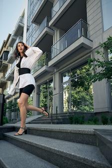 Снизу вид модной брюнетки кавказской женщины, спешащей возле офисного здания, глядя в сторону. молодая женская модель в велосипедных шортах, сандалиях на каблуках, галстуке и белой рубашке бежит вниз.