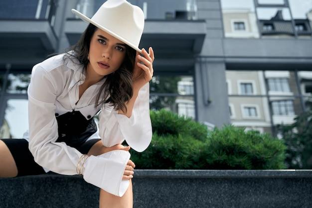 Вид снизу молодой модной женщины, позирующей возле офисного здания с зелеными кустами на городской улице. стильная женская модель в белой рубашке, шляпе, корсете и велосипедных шортах.