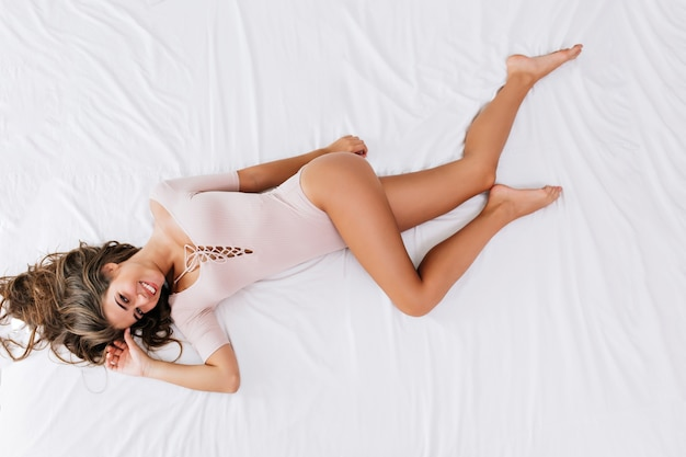 From above brunette girl with long hair laying on white bed in sensual clothes. she has snow white smile, looking .