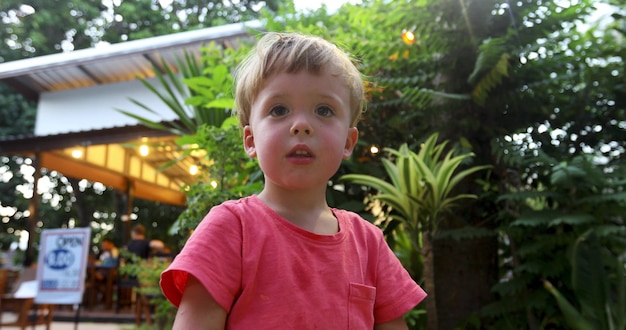 From below of cute infant boy in pink t-shirt standing on tropical terrace with green foliage on background