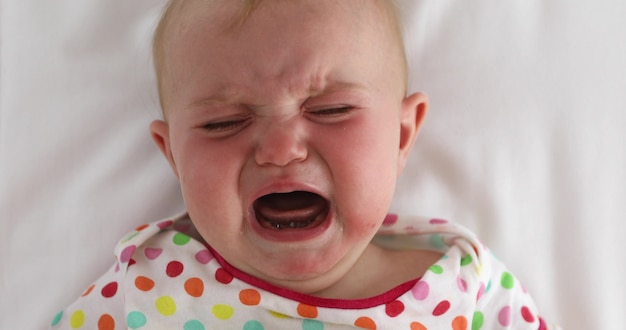 From above cute infant in colorful clothing crying while lying down on white bed sheet
