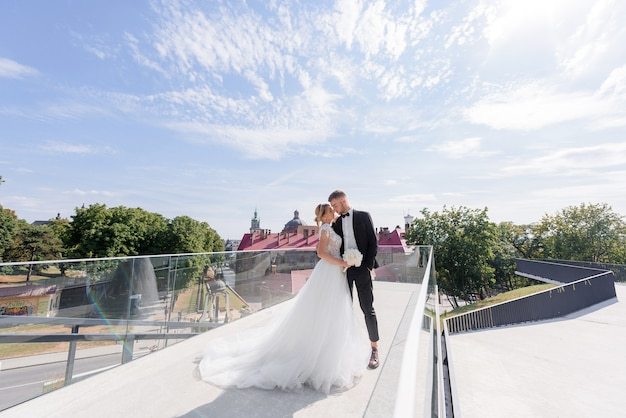 From a distance view of beautiful newlyweds hugging on the urban background
