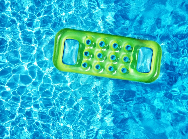 From above drone view of bright green inflatable mattress floating on blue water surface of swimming pool in sunlight in summertime