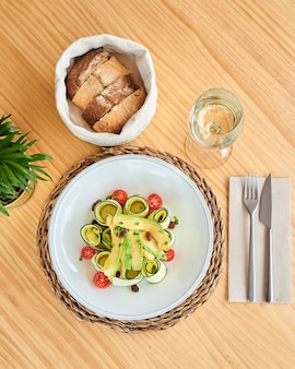 From above fresh raw zucchini salad with tomatoes and avocado accompanied by a glass of white wine and a cloth basket with bread