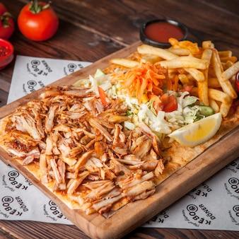 Da sopra pezzi di pollo fritto con limone e patatine fritte e insalata nel piatto di legno