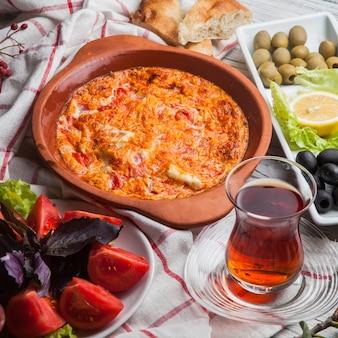 Da sopra uova fritte con pomodori con un bicchiere di tè e pomodori e olive assortite nel piatto di argilla