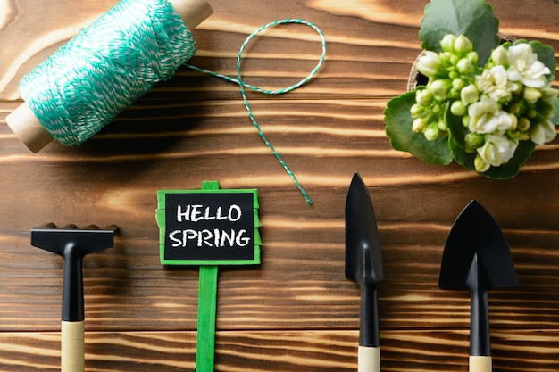 From above hello spring sign and tools for gardening on wooden table