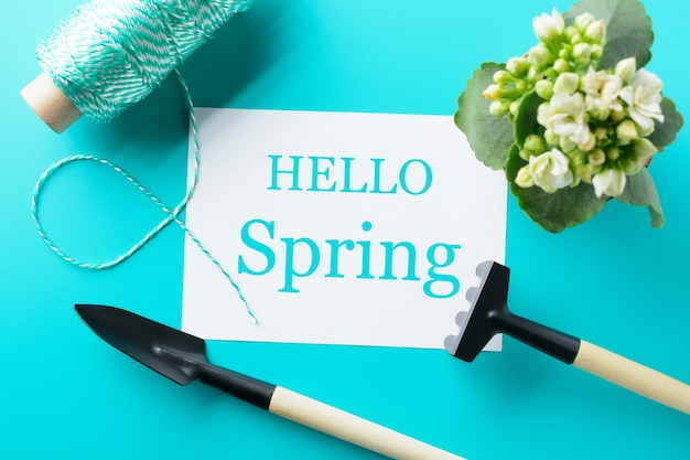 From above hello spring words and different instruments for gardening on the turquoise table