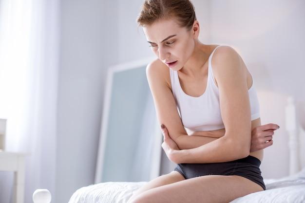 От голода. подавленная грустная женщина, держащая ее живот, чувствуя боль