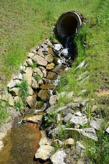 From a large concrete pipe in the hill, a spring with clean water flows out and flows along a specially laid gutter made of stones.