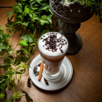 From above latte with cinnamon and chocolate chips and grape branch in glass cup