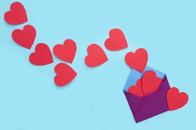 한 봉투에서 붉은 마음이 많이 나옵니다. 공예 봉투. 단조롭게. 텍스트 복사 공간