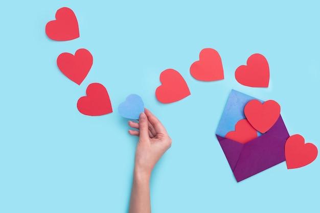한 봉투에서 소녀의 손에 담은 푸른 하트 하나에 붉은 하트 많이 나간다