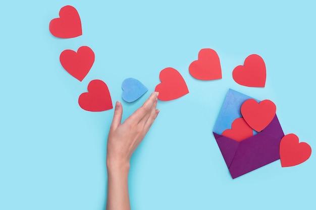 하나의 봉투에서 소녀의 손이 잡고 싶은 푸른 하트 하나로 붉은 하트를 많이 나간다