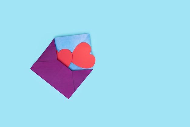 하나의 봉투에서 두 개의 붉은 마음이 나옵니다. 공예 봉투. 단조롭게. 텍스트 복사 공간