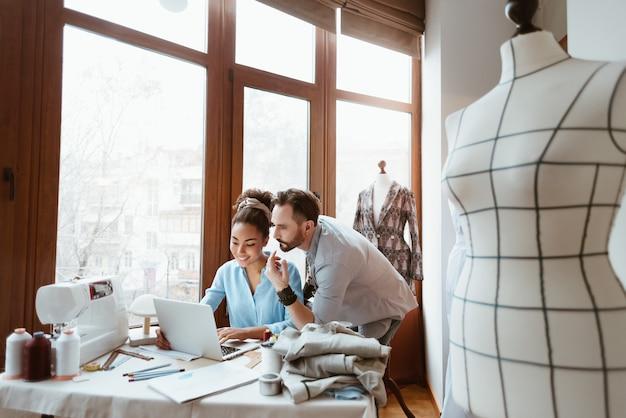 デザインスタジオで紙からノートパソコンの男性と女性まで