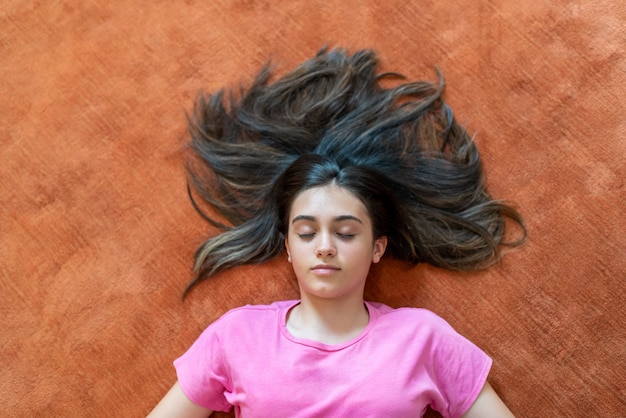 From above of peaceful female teenager with long dark hair lying with eyes closed on orange floor