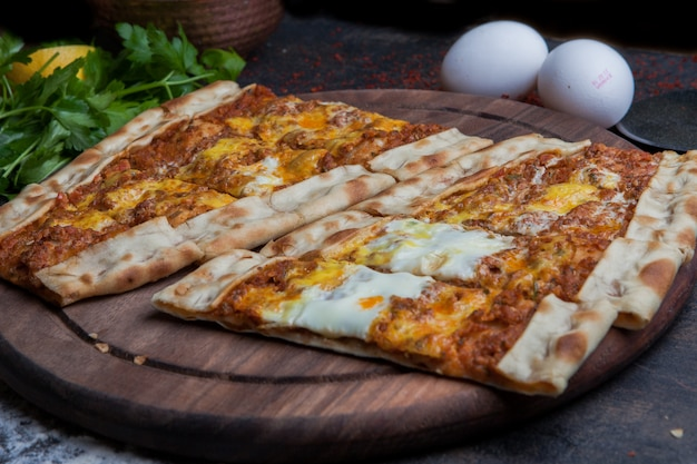 From above pide with minced meat and eggs and parsley and pizza knife in wooden food tray