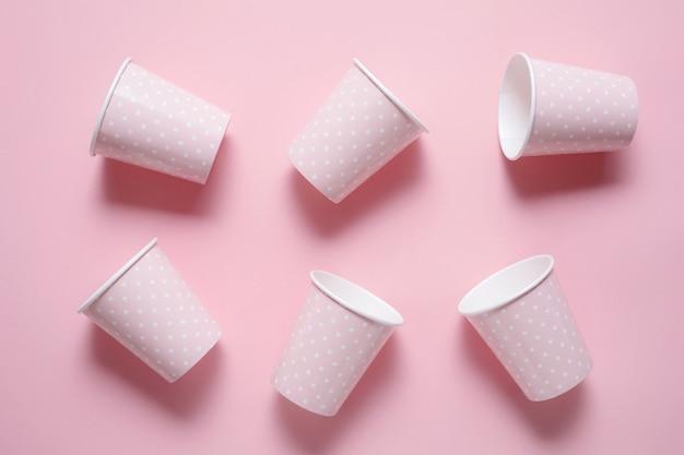 ピンクの背景に6つのピンクの紙の飲用カップから