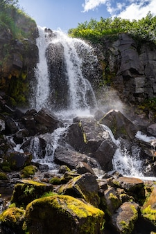 From a small stone massif, water flows down a pile of stones, where there is almost no water on the stones