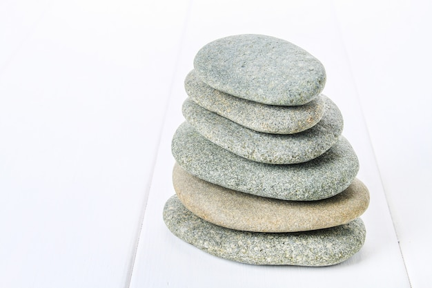 From spa stones make balances pyramids on white wooden background.