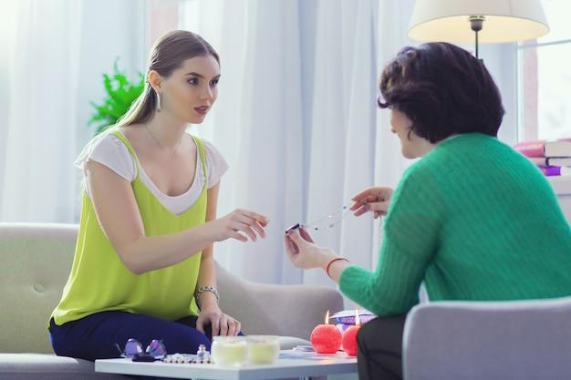 Из особого камня. милая молодая женщина берет волшебное ожерелье во время разговора с гадалкой