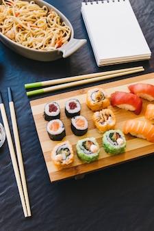 Dall'alto sushi vicino a notebook e noodles